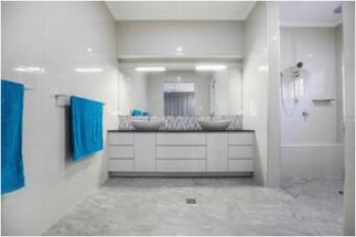 Bathroom remodelating involving floor and wall retiling. White ceramic tiles.